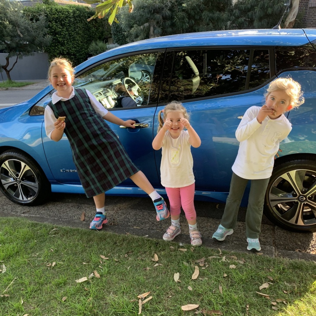 Children in front of a blue car