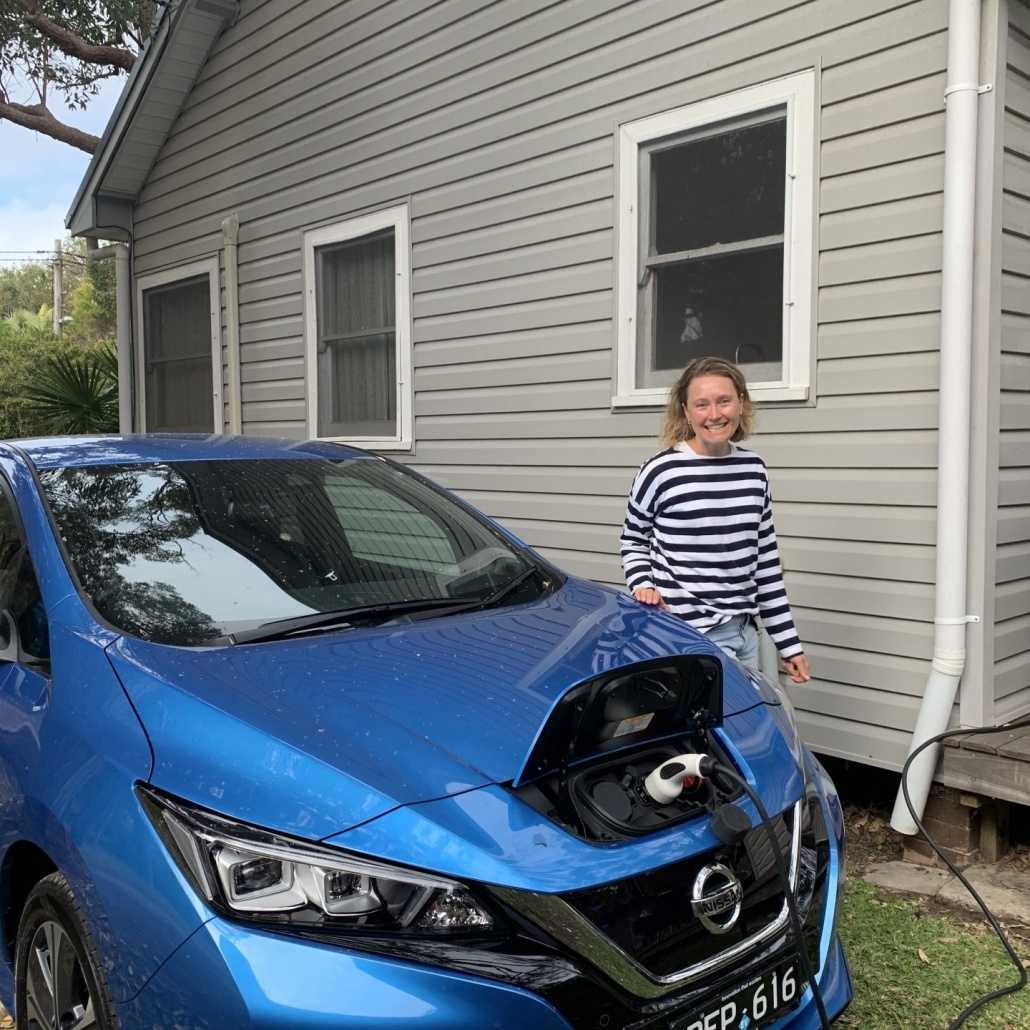 lady charging a blue electric vehicle