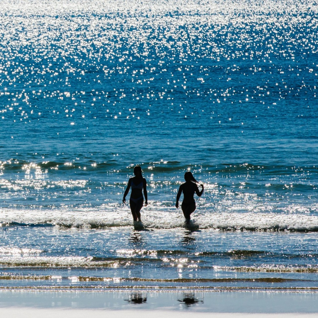Two simmers in the ocean in yamba